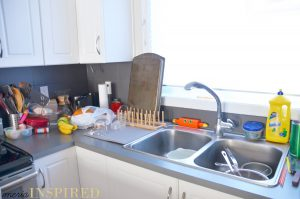 White kitchen cabinets, gray counter top, dark gray tile backsplash, metal sink filled with dishes. A sunny window is over the sink. The counters are covered with clutter - dish rack with a cookie sheet, bananas, grocery bag, coffee supplies, paper towel, a glass tiered desert dish filled with random items.